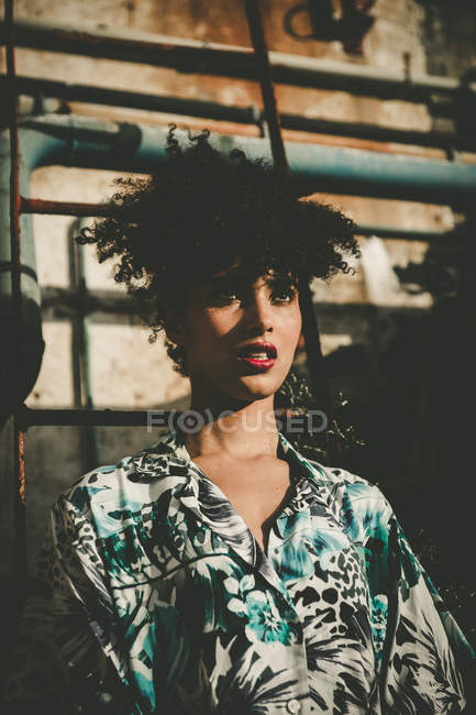 Expressive young girl with afro posing in sunlight over industrial wall — Stock Photo