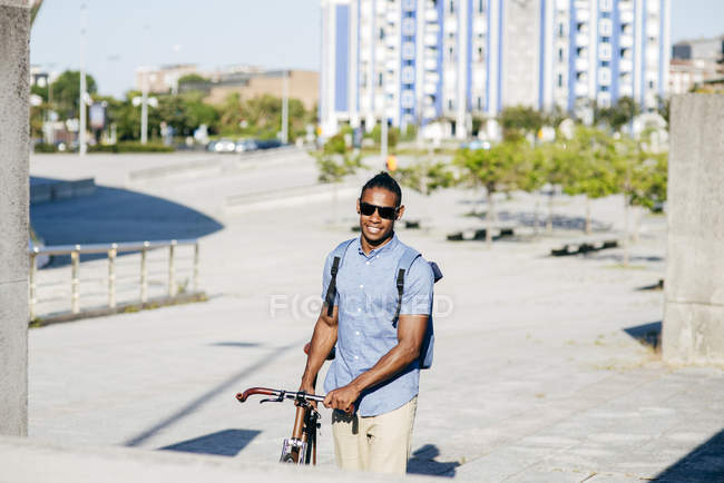 Man with bicycle in urban scene — Stock Photo