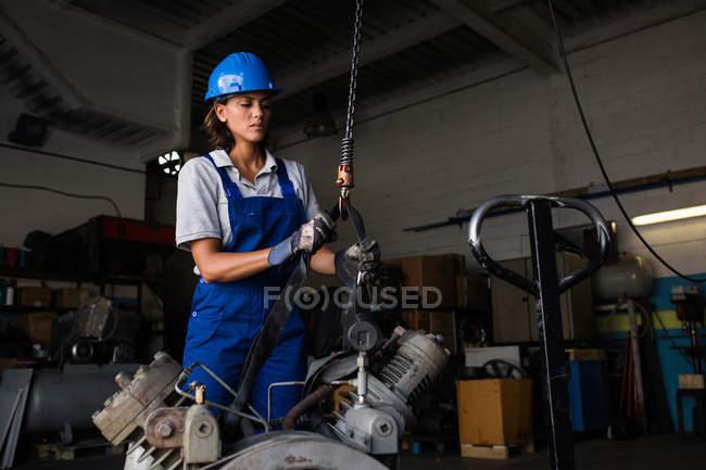 Mecánico hembra ajustando el gancho de elevación al motor del compresor - foto de stock