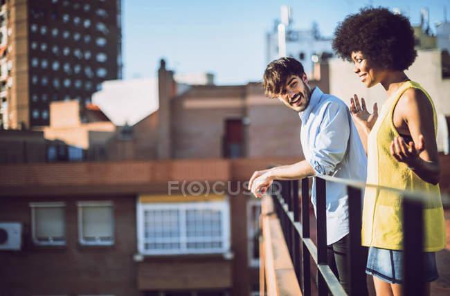 Couple Interracial s'amuser sur le toit le jour ensoleillé — Photo de stock