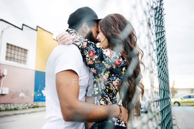 Couple de passion embrassant près de la clôture — Photo de stock
