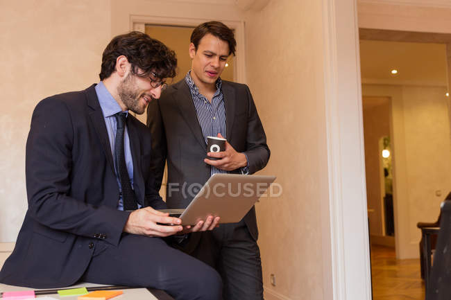 Two young coworkers in formal suits looking at laptop in office. — Stock Photo