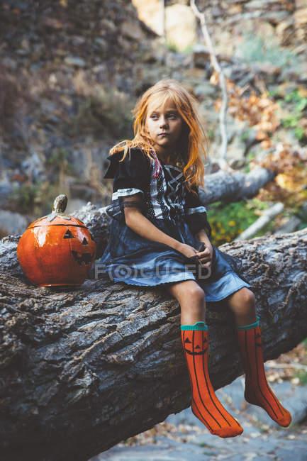 Девушка в костюме позирует на дереве — стоковое фото