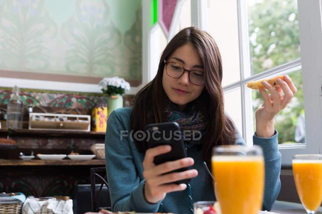 Portrait de femme brune en lunettes tenant un pain grillé et un smartphone de navigation à la table du café — Photo de stock