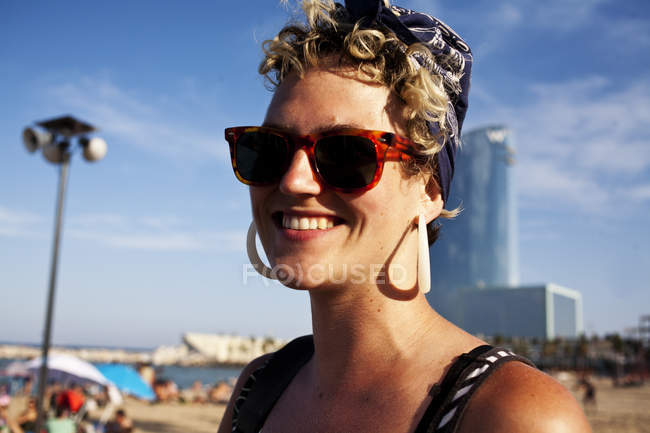BARCELONA, SPAIN - 10 July, 2011: Portrait of stylish woman in sunglasses posing on background of beach. — Stock Photo