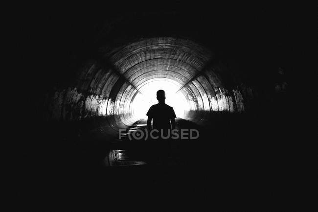 Back view of unknown person standing deep in tunnel. — Stock Photo