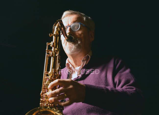 Зрелый человек играет саксофон с закрытыми глазами — стоковое фото
