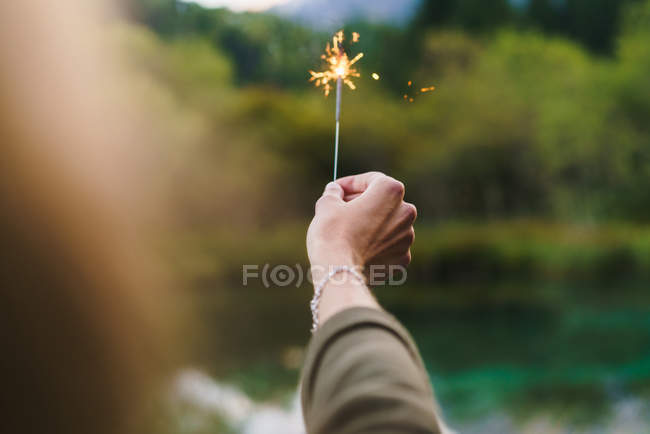 Crop hand holding sparkler on nature — Stock Photo