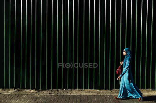 KAULA LUMPUR, MALASIA- 28 MART, 2016: Side view of woman wearing blue abaya and headscarf walking alongmetal fence. — Stock Photo