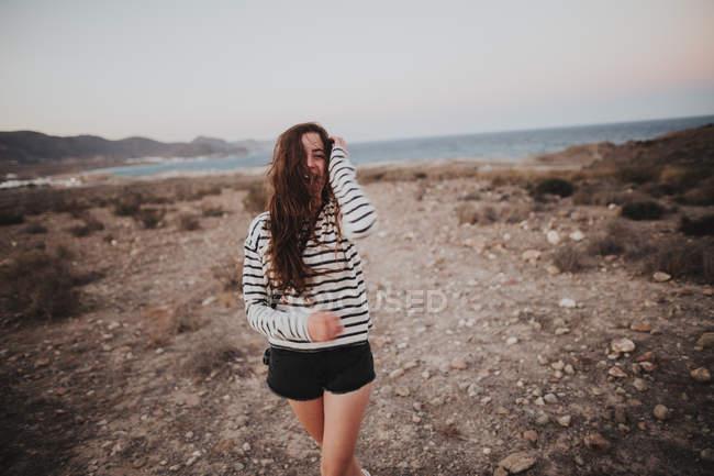 Ritratto di giovane bruna che ride camminando al mare — Foto stock