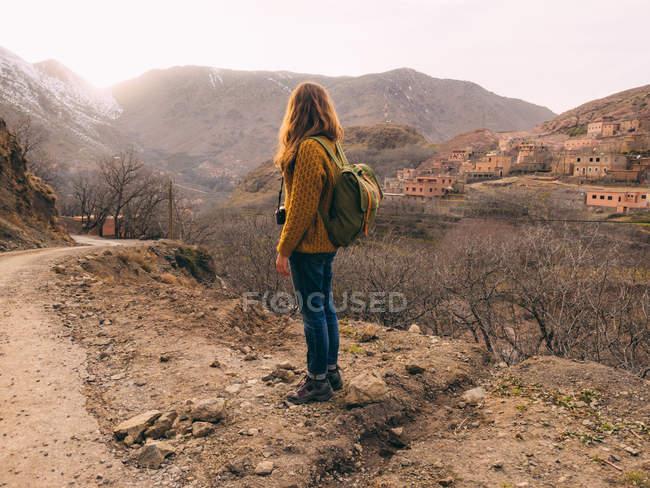 Vue latérale du touriste avec sac à dos contre la ville au paysage vallonné — Photo de stock