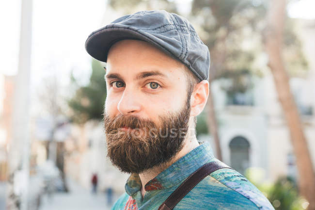 Cheerful bearded man in denim cap looking at camera at street — Stock Photo