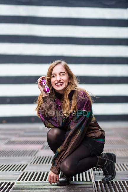 Young fashionable girl sitting in squat and holding sunglasses while laughing at camera. — Stock Photo