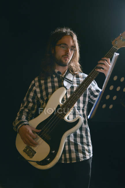 Man playing bass in stage and looking at notes — Stock Photo