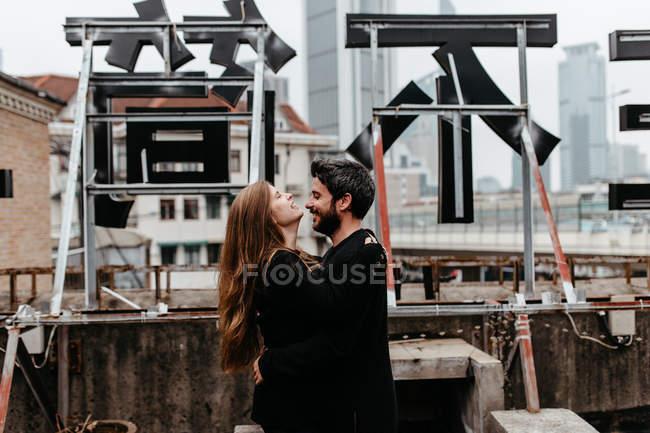 Vista laterale della coppia felice che si abbraccia sul tetto — Foto stock