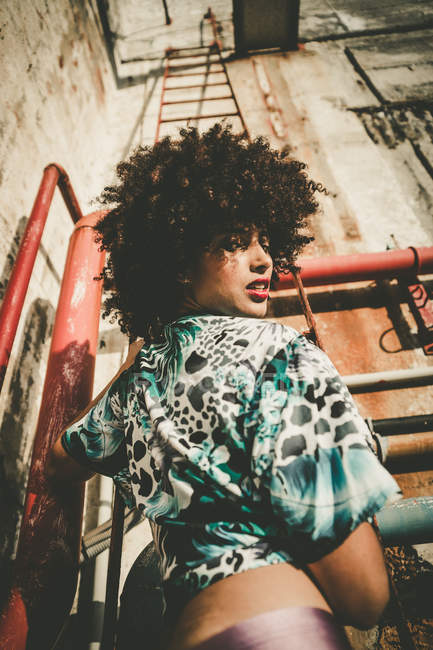 Expressive young girl with afro looking over shoulder at camera at industrial scene — Stock Photo