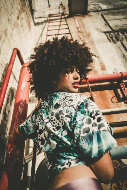 Fillette expressive avec afro regardant par-dessus l'épaule à la caméra de la scène industrielle — Photo de stock