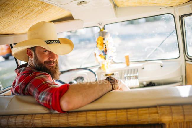 Man in cowboy hat sitting at drivers seat of retro van and looking at camera — Stock Photo