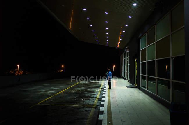MALAYSIA- 26 de abril de 2016: Vista lateral del hombre de pie sobre el pavimento del edificio con aparcamiento en la noche . - foto de stock