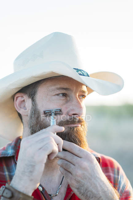 c03f6b21339 Portrait of bearded man in cowboy hat shaving with vintage double-edge  razor and looking