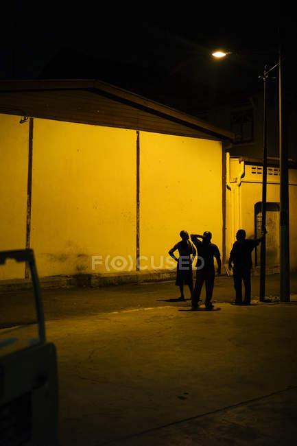 МАЛАЙЗИЯ - 21 апреля 2016 года: Отдаленный взгляд на троих мужчин, стоящих под фонарем рядом с зданиями на ночной улице — стоковое фото