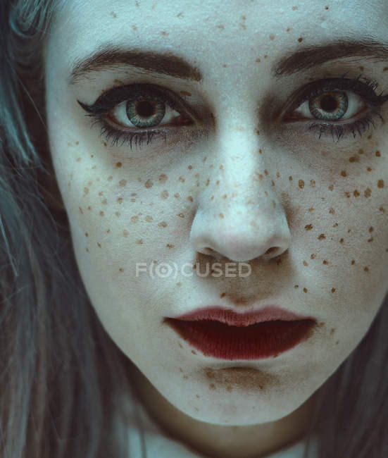 Young woman with freckles on face looking at camera. — Stock Photo