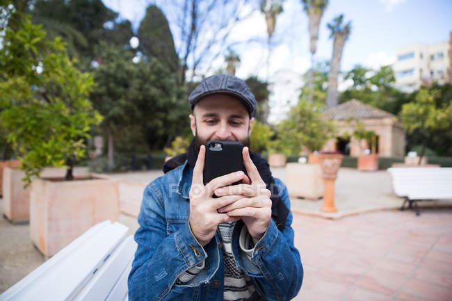 Portrait of man in stylish outfit taking photo with smartphone on background of street. — Stock Photo