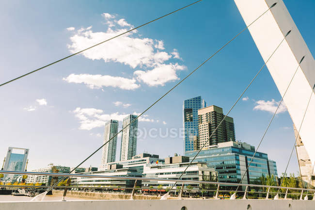 Downtown skyscrapers against sky seen from suspension bridge — Stock Photo