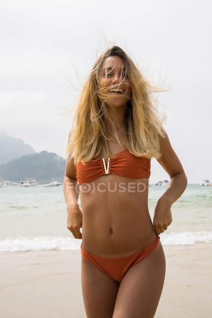 Smiling blonde girl in bikini walking on beach and looking at camera — Stock Photo