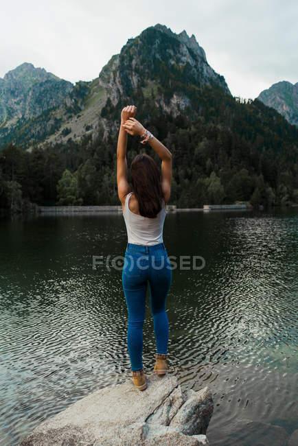 Femme posant sur la pierre au lac de montagne — Photo de stock