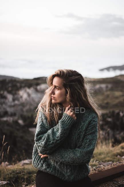 Accogliente donna bionda seduta sul ciglio della strada — Foto stock