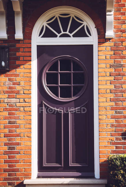 Purple door with round window — Stock Photo