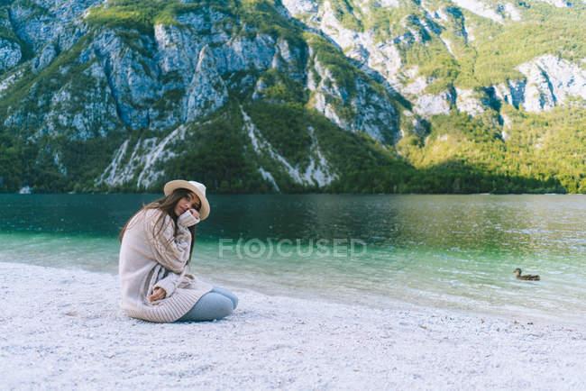 Жінка сидить на березі озера і, дивлячись на камеру — стокове фото