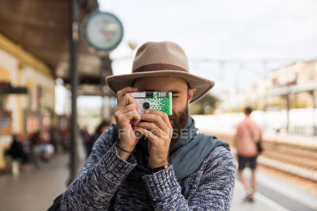 Портрет бородатого мужчини носити капелюх, що робить постріл з Ломографія камери на залізничний вокзал — стокове фото