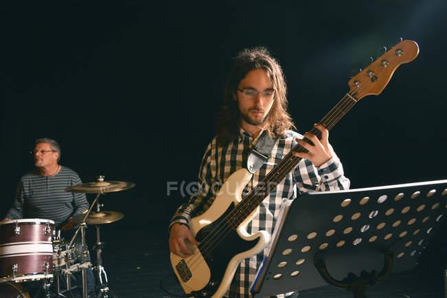 Музыканты играют на гитаре и ударных на сцене — стоковое фото