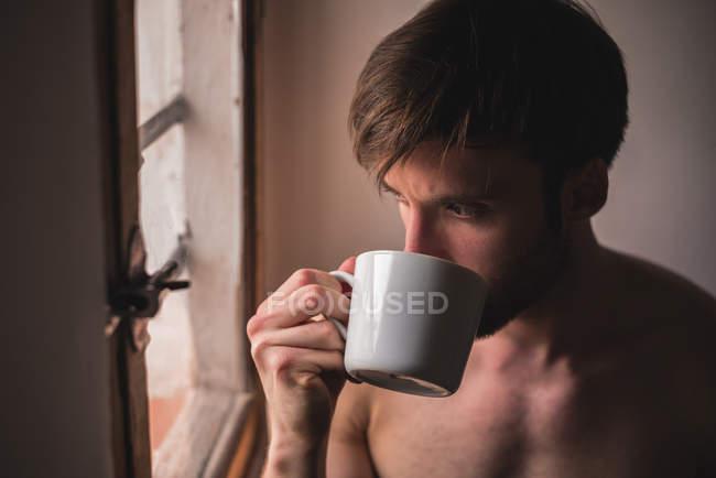 Вдумчивый молодой человек пьет кофе и смотрит в окно — стоковое фото