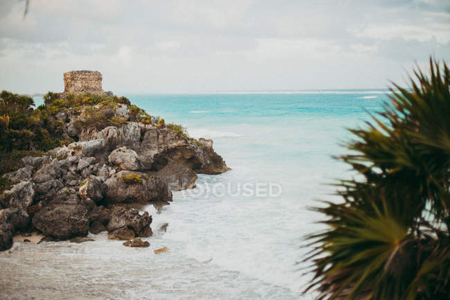 Landscape of tropical bay with turquoise ocean  water surfing on sandy beach with cliffs. — Stock Photo
