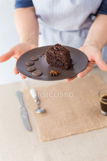 Cook holding plate with cake — Stock Photo
