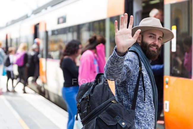 Портрет бородатого мужчини в капелюсі, несучи рюкзак і махає рукою на камеру — стокове фото