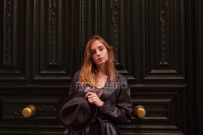 Jeune fille regardant la caméra et posant par des portes ornées — Photo de stock