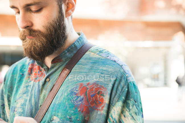 Crop bearded man in variegated looking down — Stock Photo