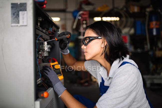 Side view of female mechanic in googles using screwdriver to fix compressor engine — Stock Photo