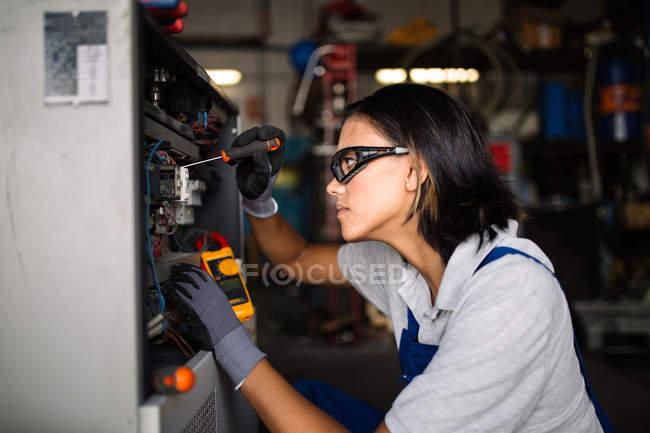 Vista lateral de hembra mecánico en googles con destornillador para fijar el motor del compresor - foto de stock