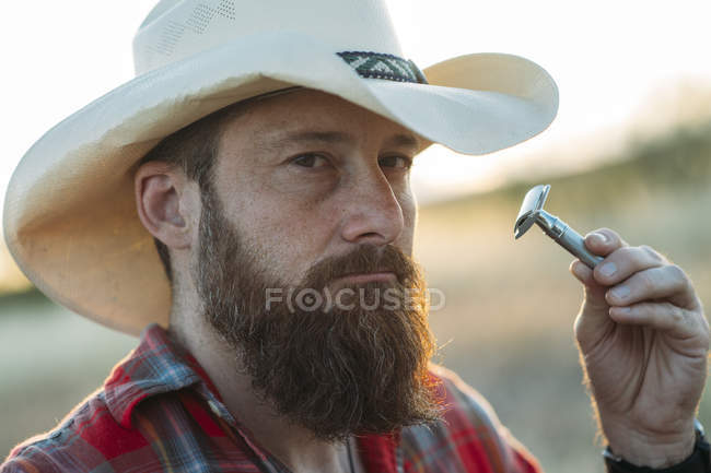 Portrait of bearded man in cowboy hat shaving with vintage double-edge razor — Stock Photo
