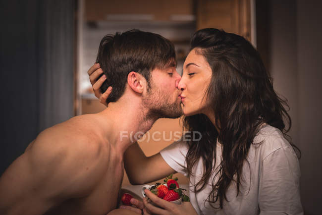Young pair kissing and holding cup of strawberry — Stock Photo