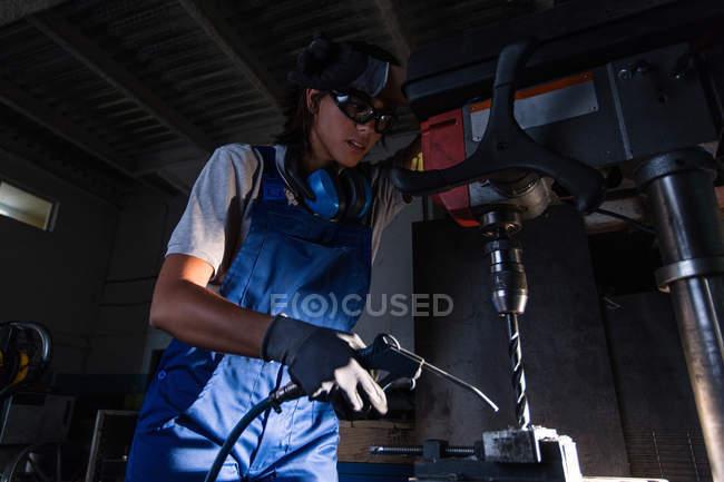 Retrato de ángulo bajo de la mecánica femenina usando pistola de aire soplado para limpiar virutas de taladro tipo columna - foto de stock