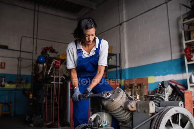 Female mechanic fixing compressor enginge with wrench — Stock Photo