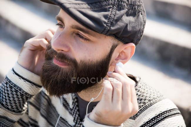 Portrait of pensive bearded man putting earphones — Stock Photo