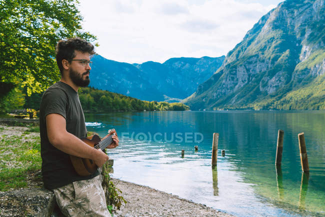 Hombre tocando la guitarra en el lago - foto de stock