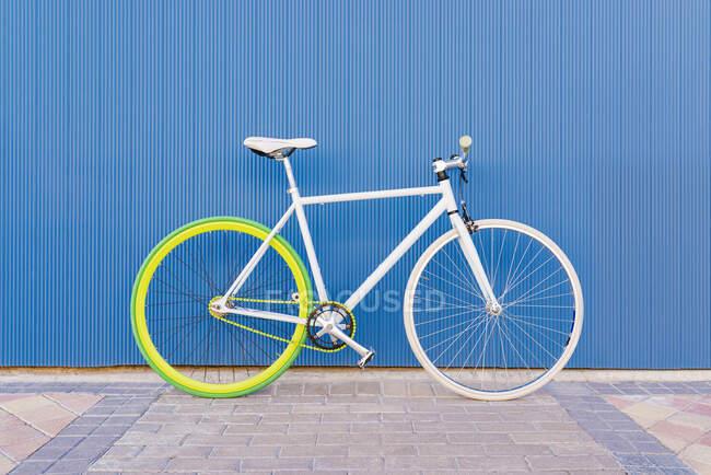 Ciudad bicicleta engranaje fijo en la pared azul. Ciclismo o desplazamientos urbanos urbanos, concepto de transporte ecológico. - foto de stock
